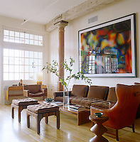 A framed photographic print is displayed against the limewashed walls of the living room above a sofa upholstered in brown corduroy