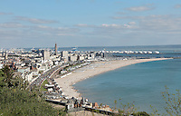 Beach and city of Le Havre, seen from Sainte Adresse, Seine-Maritime, Normandy, France. To the left is the tower of the Eglise Saint-Joseph or St Joseph's Church, built 1951-58 as a memorial to the 5000 citizens of the town who died during the Second World War, designed by Auguste Perret, 1874-1954, and Raymond Audigier. Either side are the apartment blocks at Porte Oceane, completed 1956, also designed by Perret, with the docks of the port behind. Perret led the reconstruction of Le Havre in the 1950s, after the town was completely destroyed in WWII. The centre of Le Havre is listed as a UNESCO World Heritage Site. Picture by Manuel Cohen