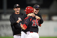 Batavia Muckdogs pitcher Steven Farnworth jumps on Blake Anderson (26) with Kyle Keller (35) in the background after a game winning walk off hit during a game against the Williamsport Crosscutters on August 27, 2015 at Dwyer Stadium in Batavia, New York.  Batavia defeated Williamsport 3-2.  (Mike Janes/Four Seam Images)