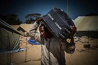 Tunisia Confine con la Libia  Campo profughi UNHCR Un rifugiato trasporta a spalle una valigia<br /> Tunisia border with Libya Refugee Camp UNHCR A refugee carries on his shoulders a suitcase
