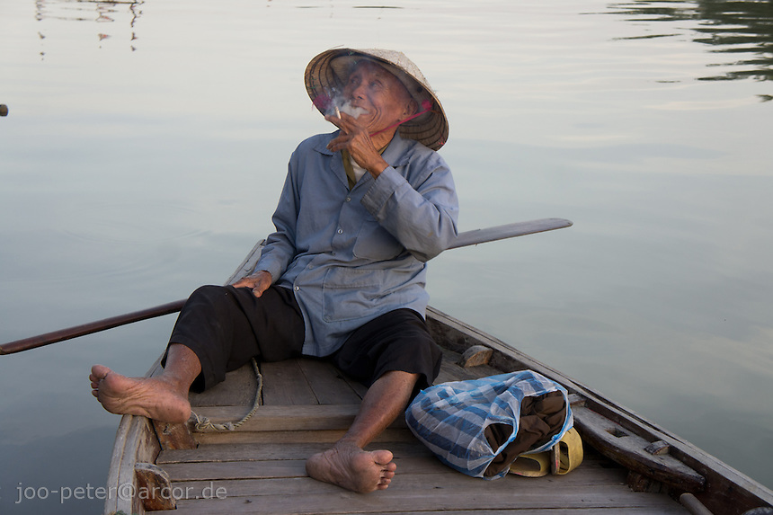old boatsman with traditional leaf hat jokes in his boat on Hoai River