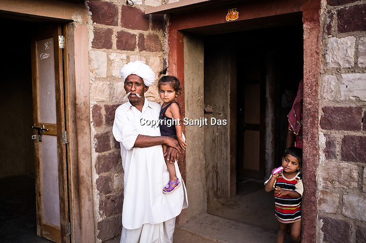 66-year-old Manganiyar artist, Lakha Khan seen spending time with his grandchildren in his house in Raneri village of Jodhpur district in Rajasthan, India. Photo: Sanjit Das/Panos