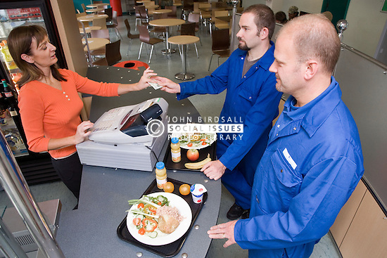 Men at a check out buying lunch in the work canteen,
