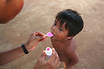 Xingu Indian child being given oral vitamin supplements, Amazon Basin, Brazil.