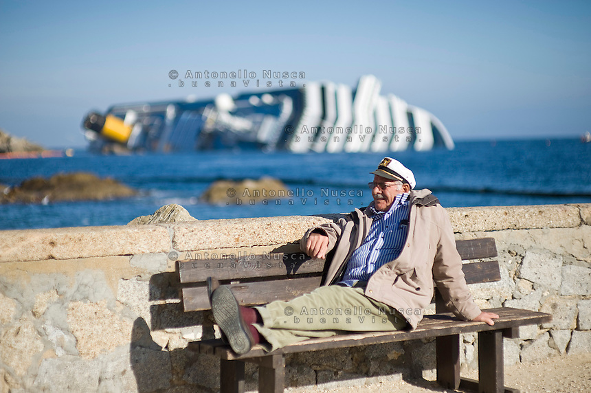 Isola del Giglio, Italy, January 17, 2012. .An old man take a rest at the port of Giglio with .