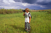 Zambia, Africa. Woman tourist with Olympus camera taking a picture in papyrus reed wetland.