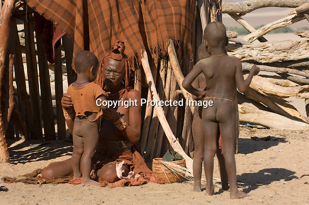 The Himba are a minority group in Namibia, representing less than one per cent of the population. They cover their skin with an ochre dust and never wash, water being in very short supply in the near-desert where they live. The women go bare-breasted and small boys wear little but a loin cloth.