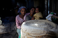 Genneth, 28 years old, living with HIV and mother of two children, poses in front of the result of the days's work with her two children, 14 and 3 years old after baking njera, a traditional ethiopian pan cake made out of tef and at the base of ethiopian diet, next to her compound as part of an income generating activity supported by the american NGO Save the Children US along the high risk corridor  in Dukam, close to Debre Zheit, Ethiopia on tusday March 10 2009..Save the Children US manages a vaste rrange of activities in support of vulnarable people that live along the truck route that connects Addis Ababa, Ethiopia's capital to the port of Djibouti. Ethiopia, a land locked country depends on the Djibouti port for most of its imports and exports.
