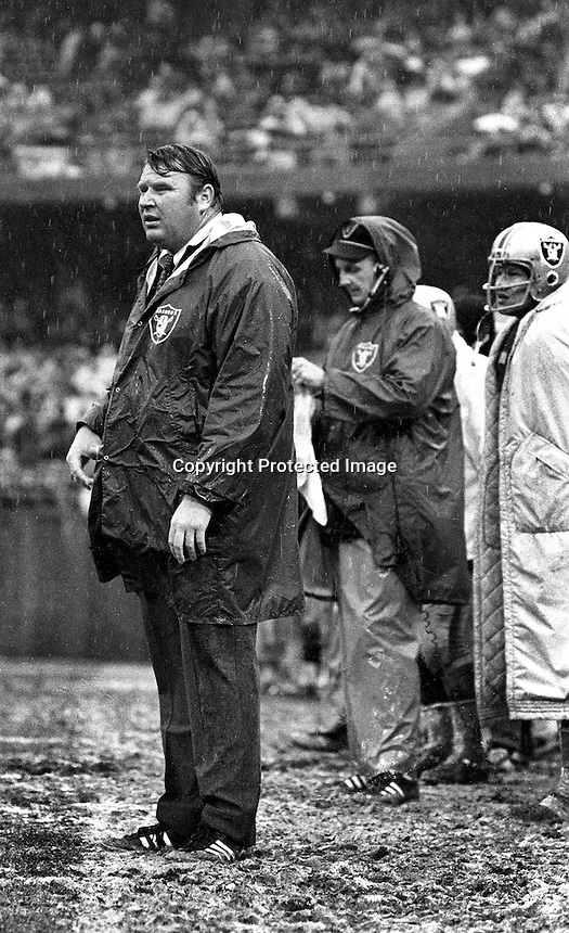 Oakland Raider coach John Madden standing in the rain.on the sideline at the Oakland Alameda County Coliseum .during 1970 game. (photo by Ron Riesterer)