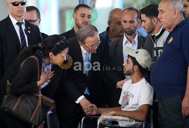 United Nations (UN) Secretary General Ban Ki-moon (C) greets a Palestinian on a wheelchair as he visits Abu Hussein United Nations school at the Jabalia refugee camp in the northern Gaza Strip on October 14, 2014.  The UN chief's visit to the Gaza Strip came a day after a Cairo conference at which international donors pledged USD 5.4 billion (4.3 billion euros) to rebuild the war-ravaged Gaza Strip. Photo by Mohammed Asad