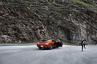 A man gets out of his Mustang car to look at Bekhal waterfall in the Gale Ali Beg Valley.