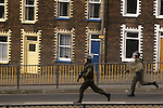 Derry Londonderry  The Troubles. 1980s. Armed  British soldiers chasing through the streets of Belfast Northern Ireland