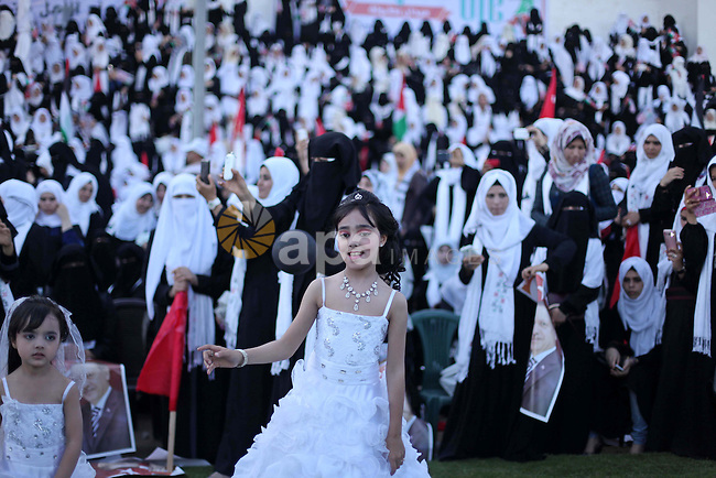A Palestinian girl attends in a mass wedding ceremony in Gaza City, on May 31, 2015. Nearly 2000 Palestinian couples were married in a ceremony funded by the Turkish government and supported by the Hamas movement. Photo by Ashraf Amra
