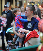 STAFF PHOTO ANDY SHUPE - Clayton Wormington of Springdale, right, holds his 2-year-old son, Connor, while visiting Santa Claus Monday, Dec. 22, 2014, in the Northwest Arkansas Mall in Fayetteville.