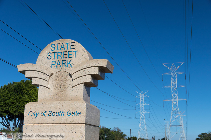 One of the entrance signs to the State Street Park in the City of South Gate, with two large transmission power lines in the background.