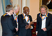 John Paul Jones, Jimmy Page, Buddy Guy and Robert Plant, four of the seven recipients of the 2012 Kennedy Center Honors, share some thoughts as they prepare to pose for a photo following a dinner hosted by United States Secretary of State Hillary Rodham Clinton at the U.S. Department of State in Washington, D.C. on Saturday, December 1, 2012.  The 2012 honorees are Buddy Guy, actor Dustin Hoffman, late-night host David Letterman, dancer Natalia Makarova, and the British rock band Led Zeppelin (Robert Plant, Jimmy Page, and John Paul Jones)..Credit: Ron Sachs / CNP