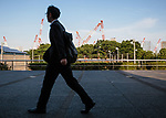 July 3, 2017, Tokyo, Japan - A picture taken on May 29, 2017 shows a businessman walking near the construction site of the new National Stadium for the Tokyo 2020 Olympics and Paralympics (in the background). According to the Bank of Japan's tankan report, confidence among the nation's largest manufacturers has risen for the third straight quarter to the greatest level in more than three years. The report showed a reading of 17 among major manufacturers which is the highest since the first quarter of 2014. (Photo by AFLO)