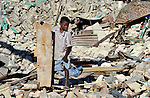 Haitians, like this boy, scavenge amidst the rubble for something of value in the devastated center of Port-au-Prince, Haiti, which was ravaged by a January 12 earthquake.