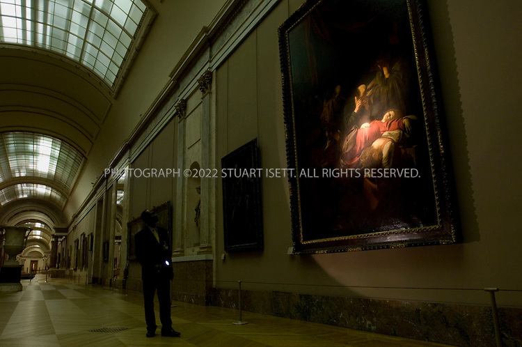4/20/2006--Paris, France..Louvre Museum  security official, Alex Crozilhac, shines his flash light on 'The Death of the Virgin' by Caravaggio, a painting featured in Dan Brown's novel 'The Da Vinci Code'. In the novel this is the location where Jacques Sauniere's body was found, in the Denon Wing of the museum's Grand Gallery...Photograph By Stuart Isett.All photographs ©2006 Stuart Isett.All rights reserved.
