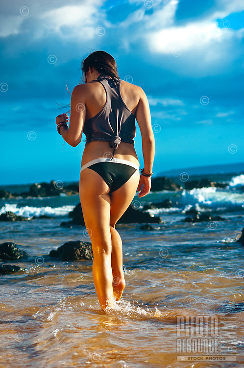 Woman walking in shallow tide pool, Maui