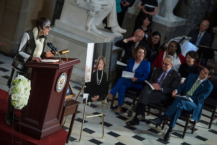 UNITED STATES - APRIL 18: Rep. Rosa DeLauro, D-Conn., speaks during a memorial service for the late Rep. Louise Slaughter, D-N.Y., in the Capitol's Statuary Hall on April 18, 2018. Slaughter, in picture, passed away on March 16, 2018, at age 88. Seated from left are, Rep. Paul Tonko, D-N.Y, House Minority Leader Nancy Pelosi, D-Calif., Rep. Gwen Moore, D-Wis., Senate Minority Leader Charles Schumer, D-N.Y., Rep. Doris Matsui, D-Calif., and Speaker Paul Ryan, R-Wis. (Photo By Tom Williams/CQ Roll Call)