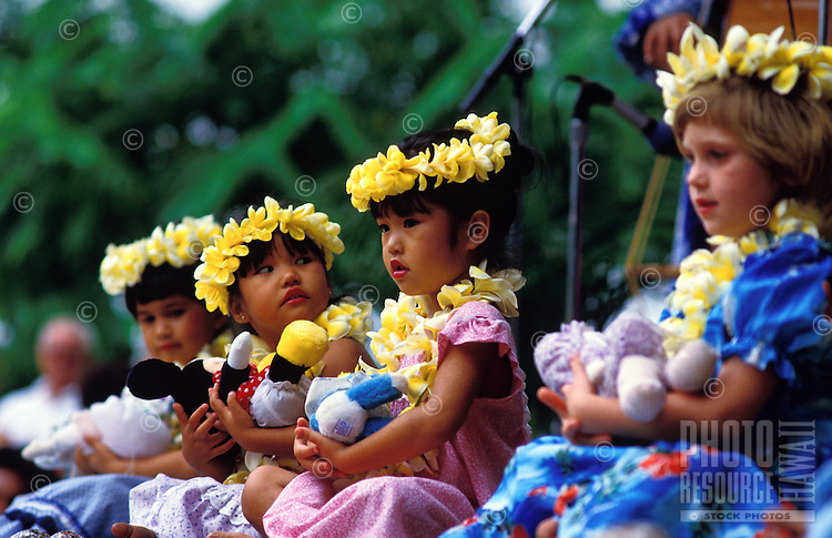 Four young island keiki hula dancers performing a noho (seated) hula, holding dolls and wearing yellow plumeria leis