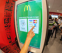 "A diner chooses her payment method at a ""Create Your Taste"" kiosk at a McDonald's in New York on Tuesday, August 4, 2015. The interactive iPad-like digital displays allow customers to customize their order with toppings, new sauces, etc. and have them delivered to their table in a few minutes. McDonald's, which has seen same-store sales drop over three years, is using the kiosks to compete with fast casual restaurants such as Chipotle, Fatburger and a host of others. (© Richard B. Levine)"