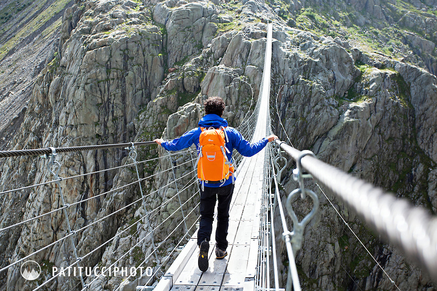 Male hiker crossing the Trift Bridge, the longest suspension bridge in Europe. Swiss Alps