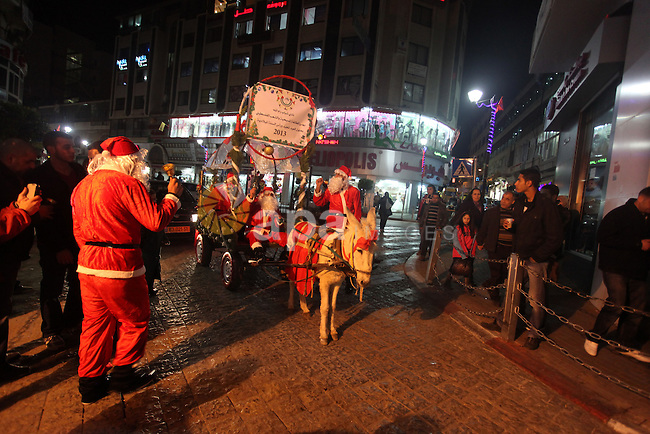 A Palestinian dressed as Santa Claus rides a cart pulled by a donkey in the West Bank city of Ramallah ahead of Christmas on December 23, 2012.Christians across the Israeli occupied Palestinian West Bank are preparing for the upcoming Christmas celebrations. Photo by Issam Rimawi