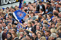A young Bath fan in the crowd waves a flag in support. Aviva Premiership match, between Bath Rugby and London Irish on September 28, 2013 at the Recreation Ground in Bath, England. Photo by: Patrick Khachfe / Onside Images