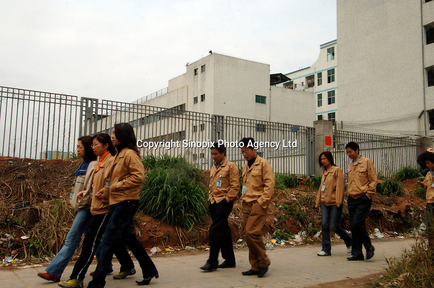 Foxconn employees pass a dorm at Taiwanese owned Foxconn plant, a high end electronic manufacture that employs well over 140,000 workers at their plant at Longhua, Shenzhen, China that consists of more than 10 large factories and 11 research units at a sprawling complex that covers several square kilometers.