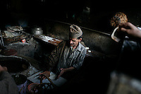 A customer waiting with money in hand as baker makes bread. Srinagar, Kashmir, India. © Fredrik Naumann/Felix Features