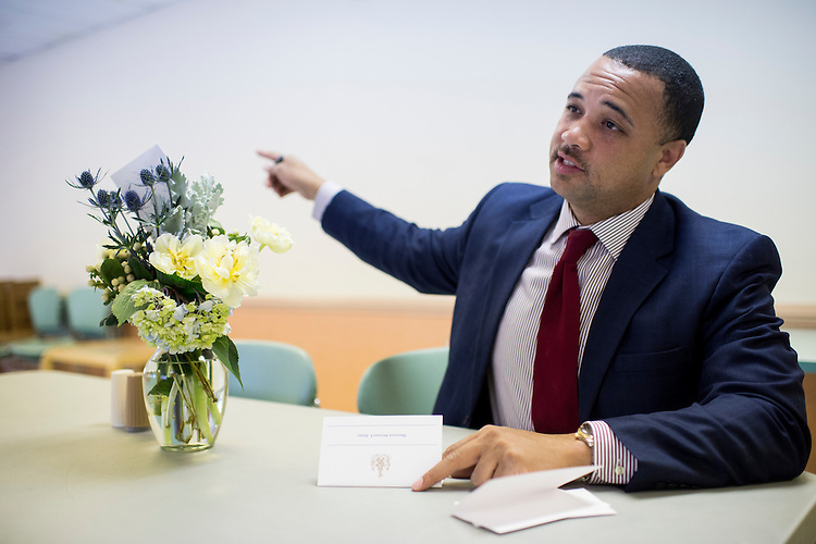 UNITED STATES - MAY 5: Maryland Del. Antonio Hayes writes notes on cards to leave on the flowers delivered by Democratic campaign consultant Martha McKenna to the Penn North Plaza senior living facility next door to the burned out CVS in Baltimore on Tuesday, May 5, 2015. In the wake of the unrest in Baltimore, McKenna organized food deliveries, and on this day, flower deliveries to senior citizen facilities in the areas of the city affected by the Freddie Gray riots. (Photo By Bill Clark/CQ Roll Call)