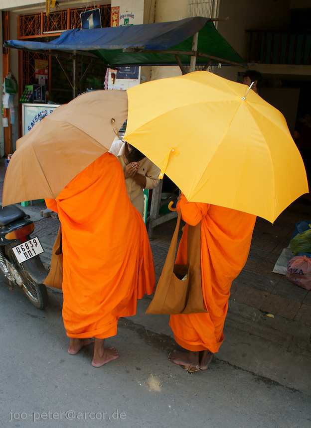 two monks with umbrella ask for donation, Phnom Penh, Cambodia, August 2011