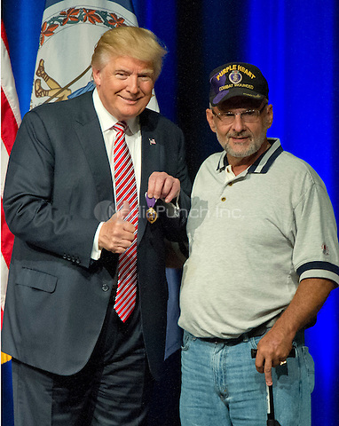 Donald J. Trump, the Republican candidate for President of the United States, displays a Purple Heart given to him by Lieutenant Colonel Louis Dorfman, right, at a campaign appearance at Briar Woods High School in Ashburn, Virginia on Tuesday, August 2, 2016.<br /> Credit: Ron Sachs / CNP/MediaPunch