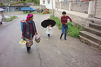 Diqing Tibetan Autonomous Prefecture, Yunnan Province, China - Members of a Tibetan family walk in the rain, August 2018.