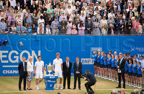 21.06.2015.  London, England. Queens Aegon Championship Tennis. Winner Andy Murrary (GBR) and runner up Kevin Anderson (RSA) take there place beside the trophy as a packet centre court looks on.