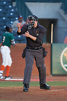 Home plate umpire Ben Fernandez makes a strike call during the South Atlantic League game between the Augusta GreenJackets and the Greensboro Grasshoppers at First National Bank Field on April 10, 2018 in Greensboro, North Carolina.  The GreenJackets defeated the Grasshoppers 5-0.  (Brian Westerholt/Four Seam Images)