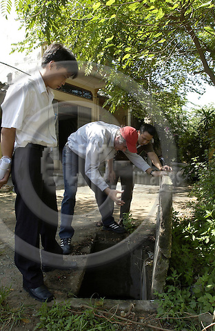 Bac Ninh-Vietnam-Viet Nam - 27 July 2005---Project area of 'Wastewater Management in Provincial Urban Centers' - Technical Assistance on behalf of GTZ by GFA Management  & Associates; here, project staff examine a rainwater drain---infrastructure, cooperation, people---Photo: Horst Wagner/eup-images