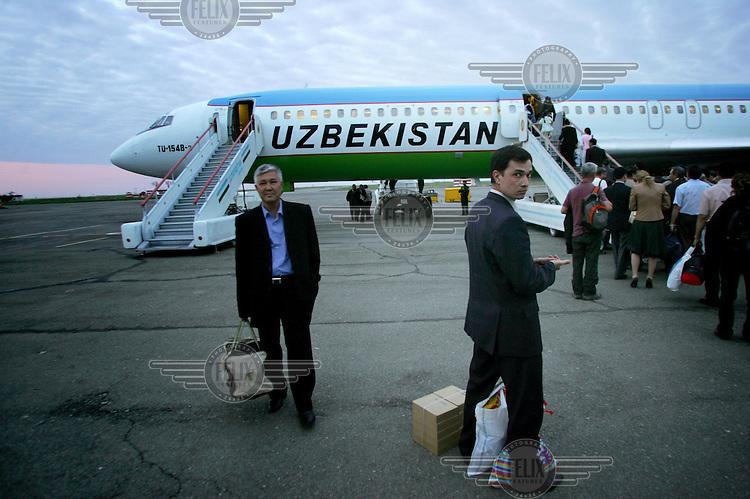 Passengers enter an Uzbekistan Airways Tupolov 154 airliner.