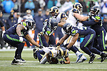 Seattle Seahawks defensive ends Michael Bennett, left, and Cliff Avril (56) and linebacker Michael Wagner (54) makes sure  St. Louis Rams running back Tre Mason (27) is down at CenturyLink Field in Seattle, Washington on December 27, 2015.  The Rams beat the Seahawks 23-17.      ©2015. Jim Bryant Photo. All Rights Reserved