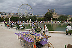 France Paris. Step Back and Be Unobtrusive.<br /> Here I employ a basic landscape technique to photograph a lake. I step back and include the foreground, so the lake has a sense of place and the lake's surface isn't so vast. The boat carriage has strong diagonal lines to lead you into the composition. The two small sailboat frame the men sitting.<br /> Learn to compose without the camera to you eye. When you think your composition looks good, then quickly fine-tune and shoot.<br /> Paris, France.