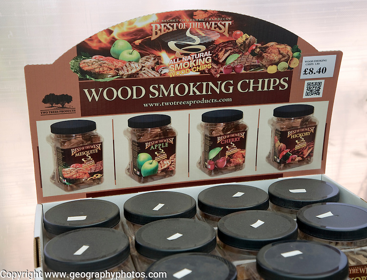 Containers of wood smoking chips on display in a garden centre, UK