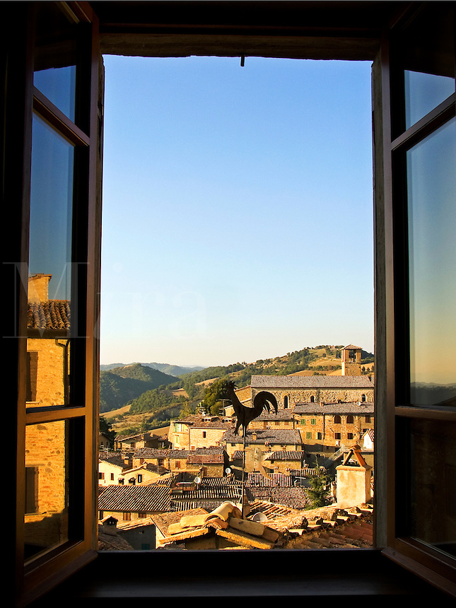 Rooftop view from inside looking out of the Umbrian hilltown of Montone Italy framed through open windo
