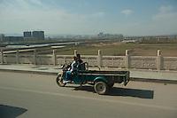Daytime landscape view of a man and a woman in a motorized tricycle in the street in Dàtóng Shì Chéng Qū in Shānxī Province, China  © LAN