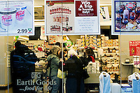 Shoppers inside D'Agnostino's purchase food, while outside a group of activists called Freegans search through the store's trash for reusable refuse.