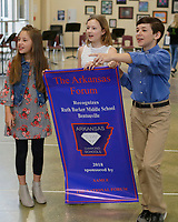 NWA Democrat-Gazette/DAVID GOTTSCHALK Bella Watkins, a sixth grade student at Ruth Hale Barker Middle School, Natalie Coon, a fifth grade student, and Noah Andrews, a sixth grade student, display the banner Wednesday, March 28, 2018, the school received recognizing them as an Arkansas Diamond School to Watch during an assembly at the school in Bentonville. Schools are recognized with this honor based on their record of academic excellence, developmental responsibility to students and social equity.