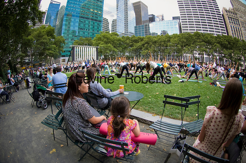 Spectators watch hundreds of yoga practitioners of all levels participate in a free yoga class given in Bryant Park in New York on Thursday, July 1, 2010. Organized by LuluLemon Athletica, the classes are offered on Thursday evenings and Tuesday mornings in the summer. (© Frances M. Roberts)