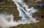 A Palestinian protester uses a sling shot to throw back a tear gas canister fired by Israeli security forces during clashes following a protest marking the Palestinian Land Day in the West Bank village of Nabi Saleh near Ramallah, March 28, 2015. Land Day commemorates the unrest that erupted in March 1976 when Israeli Arabs protested the Israeli government's confiscation of thousands of acres of Arab-owned land and in which six Arab citizens were killed by Israeli police. Photo by Shadi Hatem