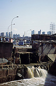 Sao Paulo, Brazil. Favela shanty town by the Tiete river; workers repairing the channel.